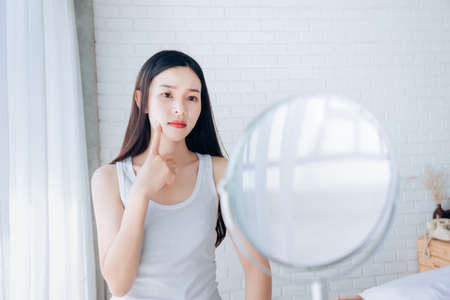 Young Asian woman squeeze acne problem face looking at mirror her without Skincare. 写真素材