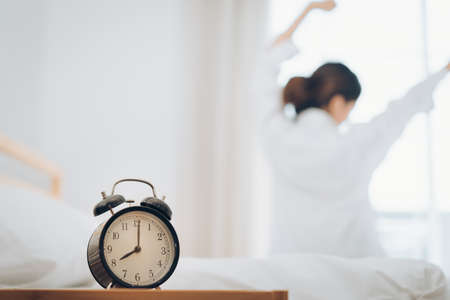 Woman wake up with alarm clock at moring her stretch on bed at home.