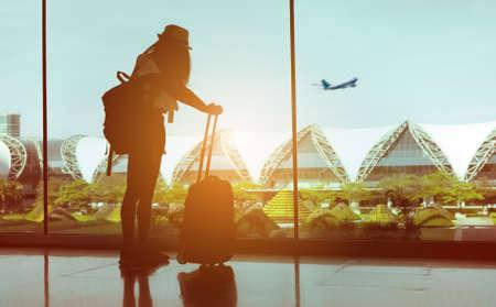 Müde Frauenreisende mit Gepäck wartendes Flugzeug am internationalen Flughafenterminal oder Mädchenjugendlicher, die im Urlaub Sommerentspannung mit Koffer und Rucksack reisen