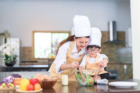 Chef profesional mamá asiática enseñando a su hijo pequeño cocinar ensalada de verduras preparar alimentos saludables en la cocina para cenar en casa estilo de vida familiar feliz.