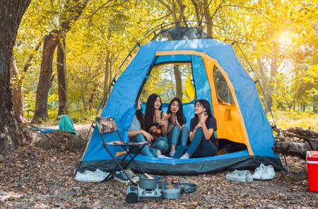若いアジアの女性の友人グループは、ウクレレを演奏する森でキャンプや休息を取り、テント料理ピクニックの人々がライフスタイルを旅する中で幸せな写真を撮ります。 写真素材
