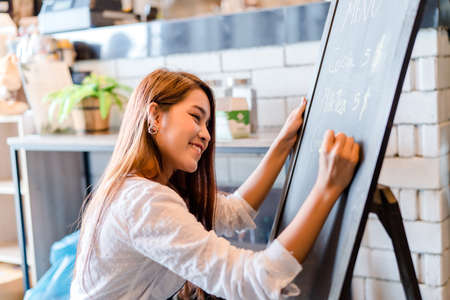 Professional Asian woman Barista writing menu front counter coffee shop occupation, part-time, job or owner business working woman happy selling and making drink beverage