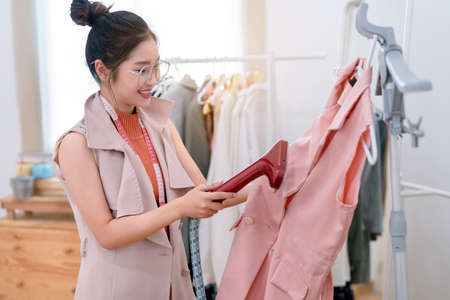 Beautiful asian woman fashion designer tailor fabric working with iron and sewing her creative design in studio tailor shop make clothes smooth, occupation owner small business concept Stok Fotoğraf