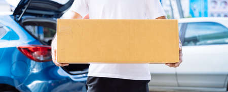 Delivery man carrying cardboard box for sending deliver to customer by transportation system hatchback car, Business of male transport sell part or product service parcel for convenience of customer