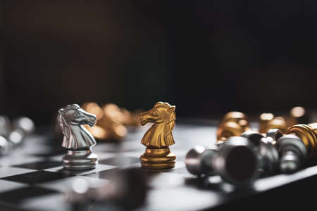 Gold and Silver Chess game knight staying on chessboard, Business planing strong concept with black background Banco de Imagens