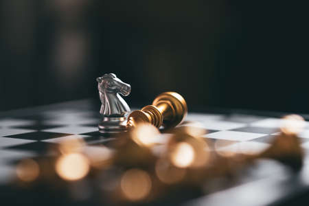 Gold and Silver Chess game knight winner staying on chessboard, Business planing strong concept with black background