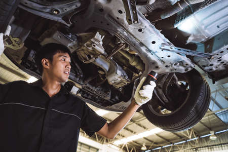 Mechanic asian man examining and service maintenance the suspension of a vehicle with flashlight, Safety inspection test engine before customer drive a car on a long journey, transportation service