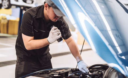 Mechanic asian man examining and maintenance to customer the engine a vehicle car hood, Safety inspection test engine before customer drive on a long journey, transportation repair service center 版權商用圖片