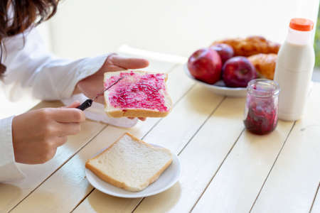 Asian woman slice jam bread in the morning and eating apple fruit,coffee healthy food breakfast meal in kitchen room fresh start the day at home healthy lifestyle concept 스톡 콘텐츠