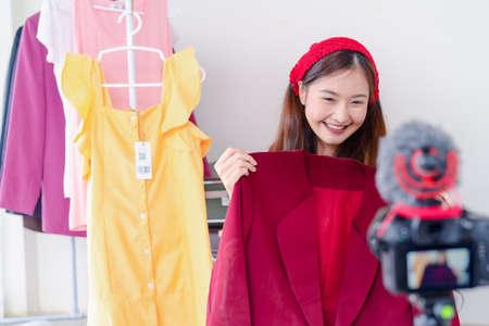 Bella giovane donna asiatica vlogger blogging presentazione abbigliamento moda video live social media registrando la sua vendita online tramite fotocamera digitale, proprietario piccola impresa imprenditore persone lifestyle