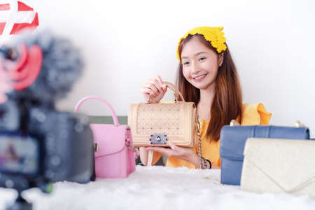 Beautiful young Asian woman vlogger blogging presentation bag fashion video live social media recording her selling online via digital camera, Owner small business entrepreneur people lifestyle Reklamní fotografie