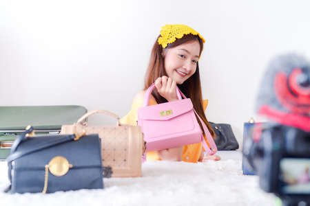 Beautiful young Asian woman vlogger blogging presentation bag fashion video live social media recording her selling online via digital camera, Owner small business entrepreneur people lifestyle Stockfoto