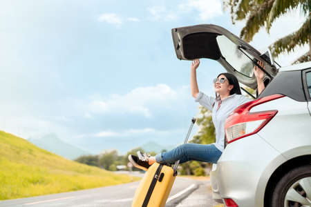 Car travel of woman journey with suitcase open hatchback car at mountain road and street in summer vacation road trip on holidays to destination, Traveler transportation vehicle people lifestyle  스톡 콘텐츠