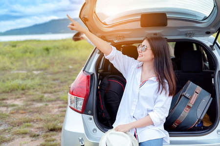 Car travel of woman journey with suitcase open hatchback car at lake river mountain and street in summer vacation road trip on holidays to destination, Traveler transportation vehicle people lifestyle 스톡 콘텐츠