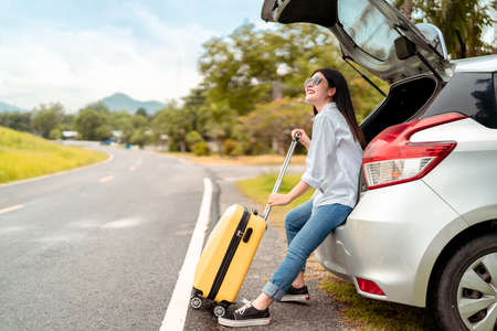 Car travel of woman journey with suitcase open hatchback car at mountain road and street in summer vacation road trip on holidays to destination, Traveler transportation vehicle people lifestyle Stockfoto