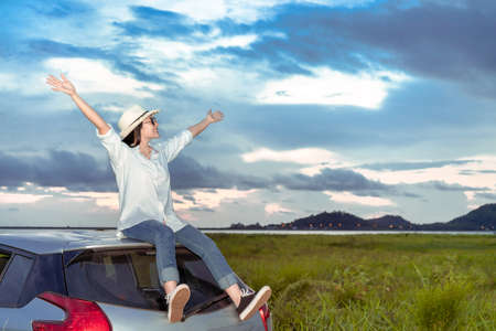 Enjoy Car travel of woman driving travel raised arms fresh air nature at lake river in summer vacation road trip on holidays to destination, Traveler transportation vehicle people lifestyle