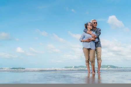 Happy asian couple senior elderly retirement resting at beach honeymoon family together happiness people lifestyle, copy space the left
