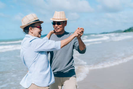 Asian couple senior elder dancing retirement resting relax at sunset beach honeymoon family together happiness people lifestyle 스톡 콘텐츠