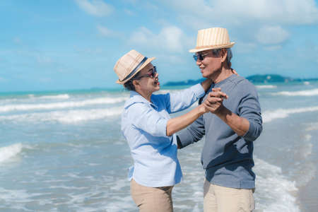 Asian couple senior elder retirement resting relax dancing at sunset beach honeymoon family together happiness people lifestyle 스톡 콘텐츠