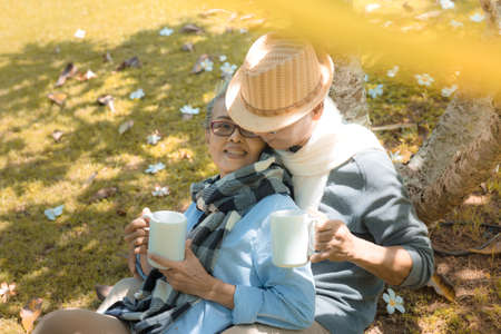 Happy family asian senior couple drinking coffee in park retirement smile in nature park relax vacation time, Elderly romantic valentine lover leisure activity healthy people lifestyle