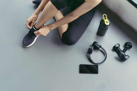 Woman sitting shoelaces with protein shake and dumbbell at fitness gym after running exercise workout for cardio and muscle building.