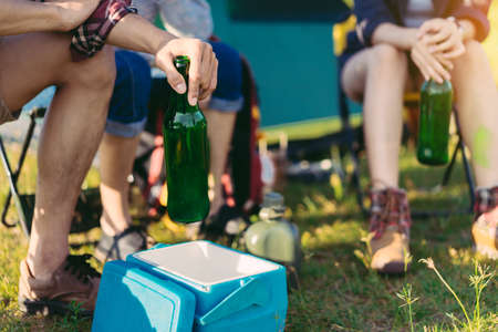 Camping group of friends drinking party travel with backpack,tent beers bottle relaxing on vacation time holiday sitting on chairs near river and mountain view.