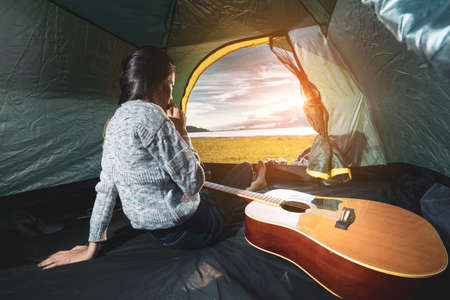 Asian Lifestyle of woman travel camping with guitar  acoustic song her sitting near mountain lake river view and beach resting relax with backpack,tent at sunset