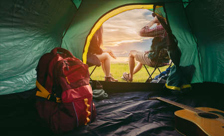 Couple lifestyle travel camping together in forest, Happy and relax young man and woman sitting on chairs near tent with backpack,guitar looking mountain river romantic traveling