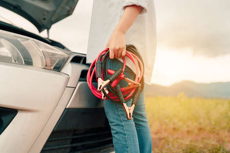 Close up Woman connecting battery cable copper wire for jumper repair and maintenance electric of engine car problem, broken her self service transportation, Vehicle stop engine between travel