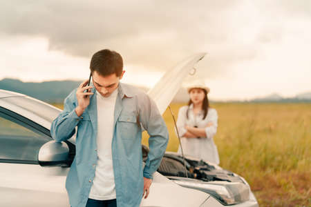 Problem Car of couple calling maintenance service assistance emergency between road trip journey in mountain lake river for examining and repair system engine fixing, Transportation travel lifestyle