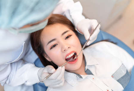 Closeup woman having dental teeth examined dentist check-up via excavator in Clinic her patient for beautiful smile 스톡 콘텐츠