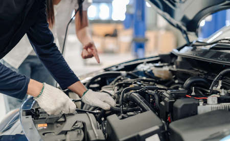 Mechanic asian man examining and maintenance to customer the engine a vehicle car hood, Safety inspection test engine before customer drive on a long journey, transportation repair Soft focus 스톡 콘텐츠