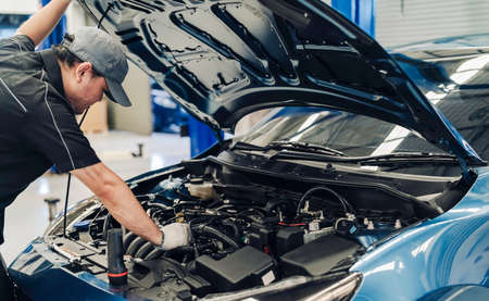 Mechanic man examining and maintenance to customer the engine a vehicle car hood, Safety inspection test engine before customer drive on a long journey, transportation repair service center 스톡 콘텐츠