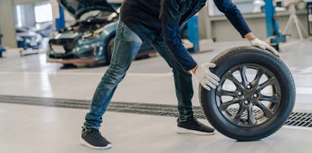 Mechanic man change a wheel tyre and service maintenance the suspension of a vehicle , Safety inspection test engine before customer drive a car on a long journey, transportation service