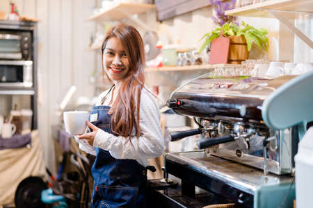 Professional Asian woman Barista preparing coffee at front counter serving coffee cup to customer occupation, part-time,job or owner business working woman happy selling and making drink beverage