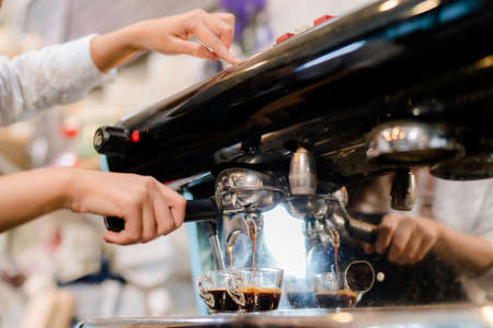 Barista preparing coffee at front counter serving coffee cup to customer occupation, part-time,job or owner business working woman happy selling and making drink beverage Stockfoto