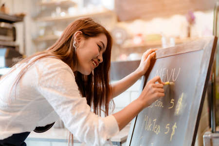 Asian woman Barista writing menu front counter coffee shop occupation, part-time,job or owner business working woman happy selling and making drink beverage