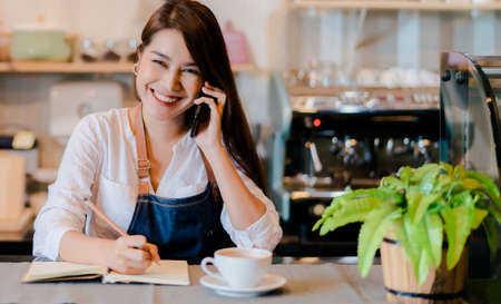 Asian woman Barista calling with customer at front counter occupation, part-time,job or owner business working woman happy selling and making drink beverage