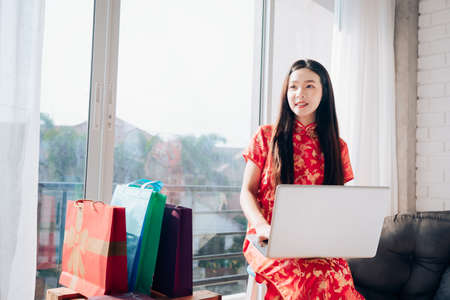 Smile of Portrait Beauty Asian Woman with Chinese dress,Qipao,Cheongsam Chinese New Year Using Laptop Computer Shopping Online near Window in Clean White Room.