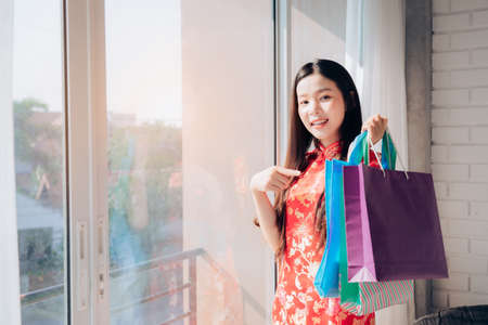Shopping Asian Woman Chinese dress,Qipao,Cheongsam Chinese New Year and hold Bag Sitting near Window in Clean White Room,Copy Space.