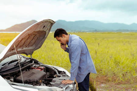 Problema Auto di un maschio che chiama servizio di manutenzione assistenza emergenza tra viaggio su strada nel fiume lago di montagna per l'esame e la riparazione del sistema di fissaggio del motore, stile di vita di viaggio di trasporto