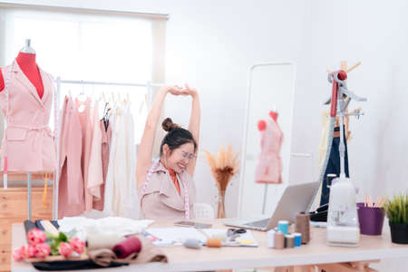 Relaxing stretching woman fashion designer tailor fabric working and sewing complete, creative design in studio tailor shop, occupation owner small business freelance concept