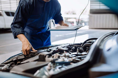 Mechanic man examining and maintenance via insurance system fix the engine a vehicle car hood, Safety inspection before customer drive on a long journey, transportation repair garage service center Zdjęcie Seryjne