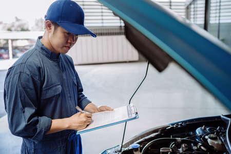 Hombre mecánico que examina y mantiene a través del sistema de seguro que repara el motor en el capó de un vehículo, inspección de seguridad antes de que el cliente conduzca en un viaje largo, centro de servicio de taller de reparación de transporte Foto de archivo