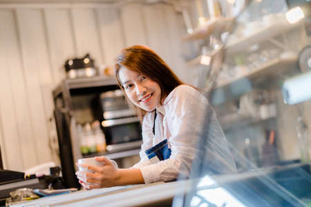 Portrait Asian woman Barista preparing coffee at front counter serving coffee cup to customer occupation, part-time,job or owner business working woman happy selling and making drink beverage