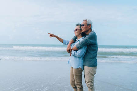 Happy asian couple senior elderly retirement resting at beach honeymoon family together happiness people lifestyle, copy space