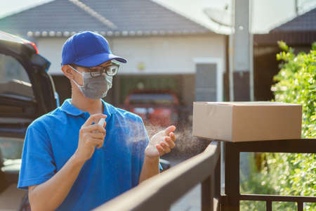 Asian Delivery man wearing mask send a package applying hand spray alcohol cleaning on before deliver cargo social distancing while the virus is spreading, Clean washing hands for protect covid-19. Foto de archivo
