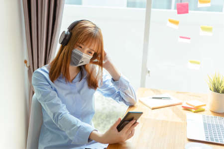 Asian woman wearing mask staying at home listening music with smartphone, headphone relaxing emotion, Prevent the spread of coronavirus quarantine work desk with computer and protective surgical mask.