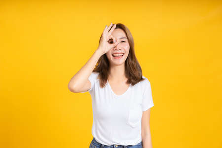 Portrait young happy asian woman ok gesture hand your eye symbol for advertising promotion sale discount in white t-shirt, Yellow background isolated studio shot and copy space.
