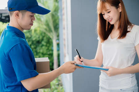 Door to door asian deliveryman express sending send a package to customer receiver sign checking shipping deliver cargo business occupation transportation shopping online concept. Imagens